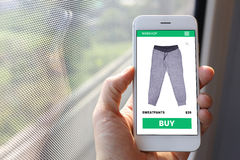 Hand holding smartphone with sweatpants ecommerce screen website Royalty Free Stock Images