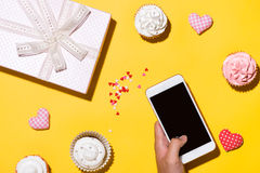Hand holding smartphone taking photo of delicious cupcake with p Stock Images