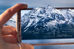 hand holding a smartphone taking a photo of a mountain landscape, a winter day