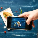 Hand holding smartphone and taking photo of sandwich. Hand holding smartphone and taking photo of appetizing vegetarian sandwich lying on flat rectangular plate Royalty Free Stock Images