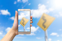Hand holding smartphone taking picture winding road sign Royalty Free Stock Image