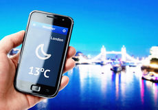 Hand holding smartphone with weather in London Stock Photo