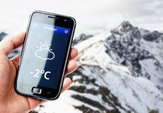 Hand holding smartphone with weather in mountains Royalty Free Stock Photo