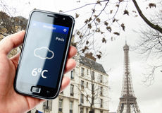 Hand holding smartphone with weather in Paris Stock Photos