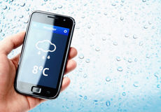 Hand holding smartphone with weather with rainy window Royalty Free Stock Images