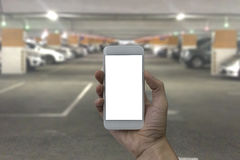 Hand holding smartphone with white blank screen over blurred Par. King lot in the mall background Royalty Free Stock Photo