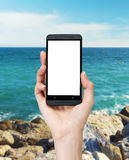 A hand is holding a smartphone with white copy space screen. Royalty Free Stock Photos