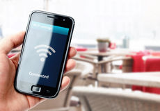 Hand holding smartphone with wi-fi connection in cafe. Hand holding smartphone with wi-fi connection on the screen in cafe Stock Photography