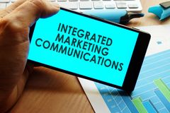 Hand holding smartphone with words integrated marketing communications. Hand holding smartphone with words integrated marketing communications and charts on a Royalty Free Stock Image