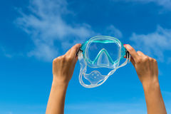 Hand holding snorkel goggles against beach Royalty Free Stock Photo