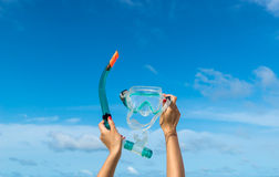 Hand holding snorkel goggles ( mask for diving) against beach and sky the sand. Royalty Free Stock Photography