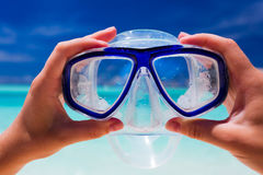 Hand holding snorkel googles against beach Stock Photography