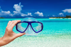 Hand holding snorkel googles against blurred beach and sky Stock Images