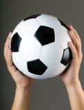 Hand holding soccer ball Stock Image
