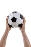 Hand holding a soccer ball on white background Royalty Free Stock Image