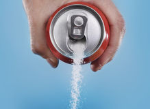 Hand holding soda can pouring a crazy amount of sugar in metaphor of sugar content of a refresh drink. On blue background in healthy nutrition, diet and sweet Royalty Free Stock Photo