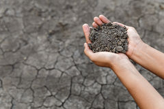 Hand holding soil. Over dry and crack soil because no water long time at here Stock Image