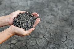 Hand holding soil. Over dry and crack soil because no water long time at here Stock Photography