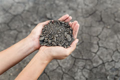 Hand holding soil. Over dry and crack soil because no water long time at here Royalty Free Stock Photography