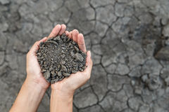 Hand holding soil. Over dry and crack soil because no water long time at here Stock Photos
