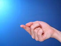 Hand holding something small on its finger Royalty Free Stock Image