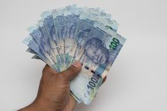 Hand holding south african rands stock image