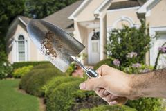 Hand Holding Spade in front of House Stock Photos