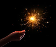 Hand holding a sparkler. On black background Stock Images