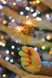 Hand holding sparklers. And Christmas tree royalty free stock images