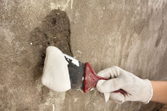 Hand holding spatula with plaster. To plastering wall Royalty Free Stock Photography