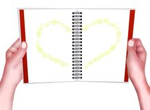 Hand Holding A Spiral Notepad with Heart Pattern Stock Photo