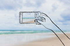 Hand holding spmartphone with beach photo on the screen Royalty Free Stock Images