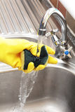 Hand holding sponge under running tap. Hand in a rubber glove holding a cleaning sponge under a running tap in a stainless steel sink Royalty Free Stock Photos