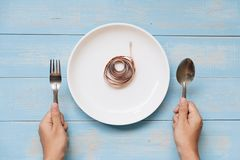 Hand holding spoon and fork above white dish with pink Measuring tape on blue pastel color wooden table. dieting , weight loss and stock photo