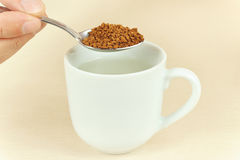 Hand holding a spoon with granulated coffee over cup of water Stock Photos