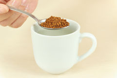 Hand holding spoon with instant coffee over the cup of water Royalty Free Stock Photo