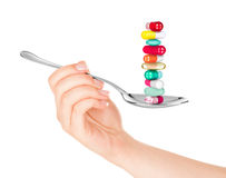 Hand holding a spoon with pills Royalty Free Stock Photography