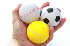 Hand holding sport balls. Masculine hand holding miniaturized rubber sport balls over white background stock image