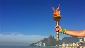 Hand Holding Sport Torch Rio de Janeiro. Hand of an athlete wearing Brazil colors sweatband holding sport torch against Rio de Janeiro Brazil skyline with Two stock footage