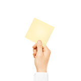 Hand holding square blank yellow sticker mock up isolated. Stick Stock Photography