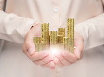Hand holding stack of gold coins Stock Image