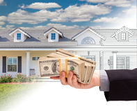 Hand Holding Stack of Money Over House Drawing Gradating Into Ph. Hand Holding a Stack of Money Over House Drawing Gradating Into Photograph stock photo