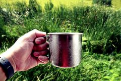 Hand holding stainless cup with blurred garden background royalty free stock photos