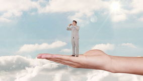 Hand holding standing businessman with binoculars against blue sky stock footage