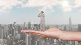 Hand holding standing businessman looking out above scyscrapers stock footage