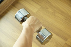 Hand holding steel dumbbell on wooden background Stock Image