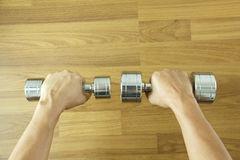 Hand holding steel dumbbell on wooden background Stock Photos