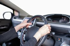 Hand holding steering wheel in modern private car with blank win. Hand holding steering wheel in modern private car with blank white windshield Stock Photo