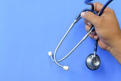 Hand holding stethoscope with blue background. Ideal for medical and health concept Royalty Free Stock Photos