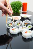 Hand holding stick with maki sushi set Royalty Free Stock Photo